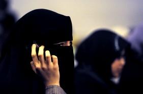 A woman wearing a burqa talks on a mobil